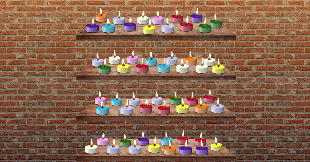selection of colourful tealight candles on shelves against a brick wall