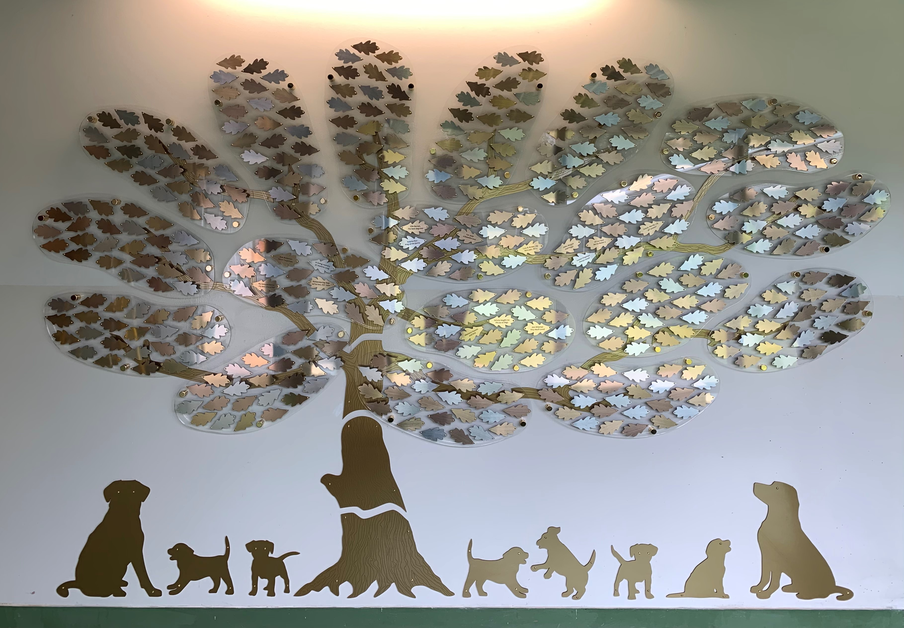 Image shows a large sculpture of a golden tree with hundreds of leaves attached to a wall. Under the tree, there are puppies playing and older dogs looking up at the leaves. Each leaf is dedicated in the name of a special pet.