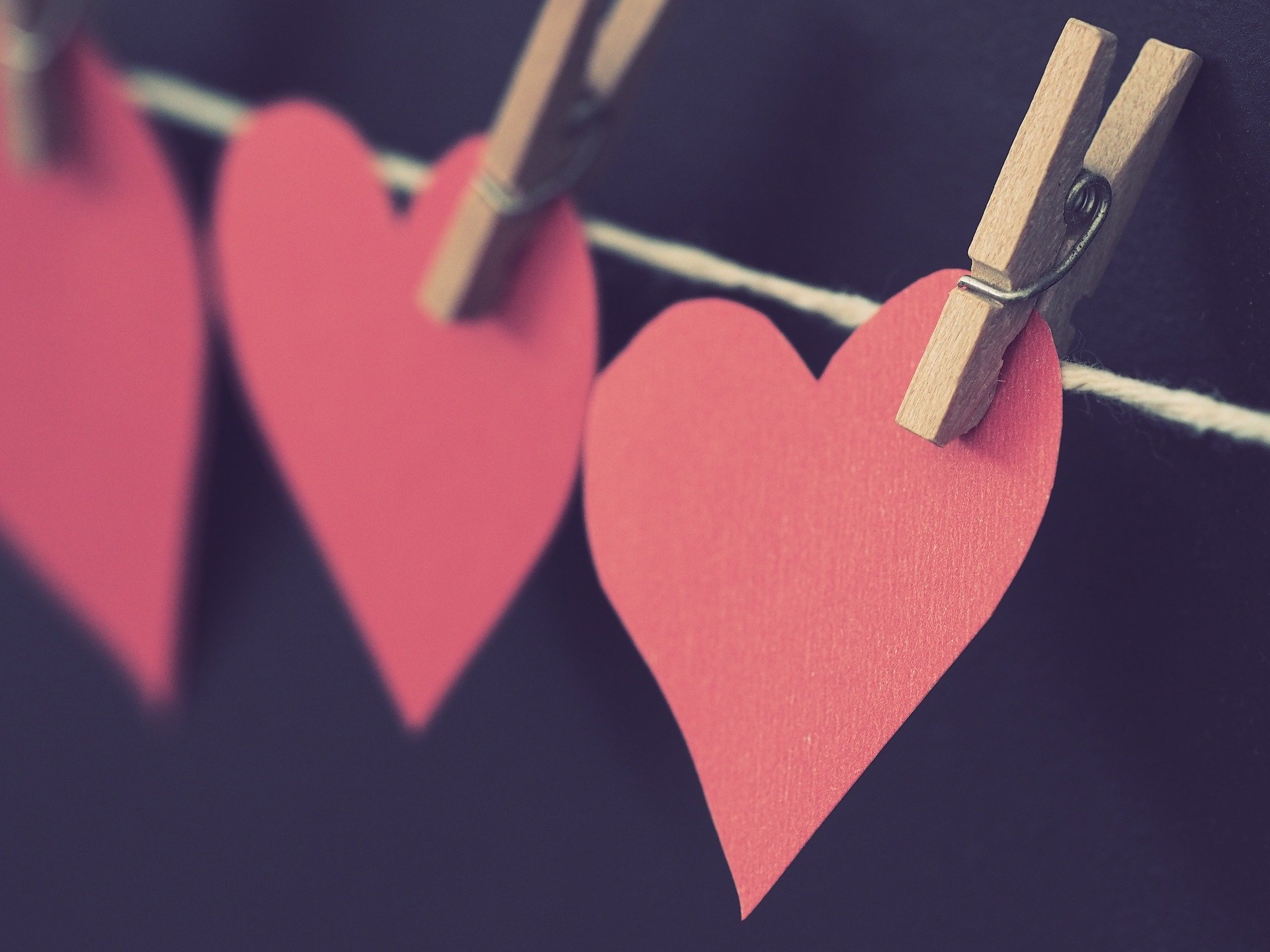 3 red paper hearts attached to a line with pegs
