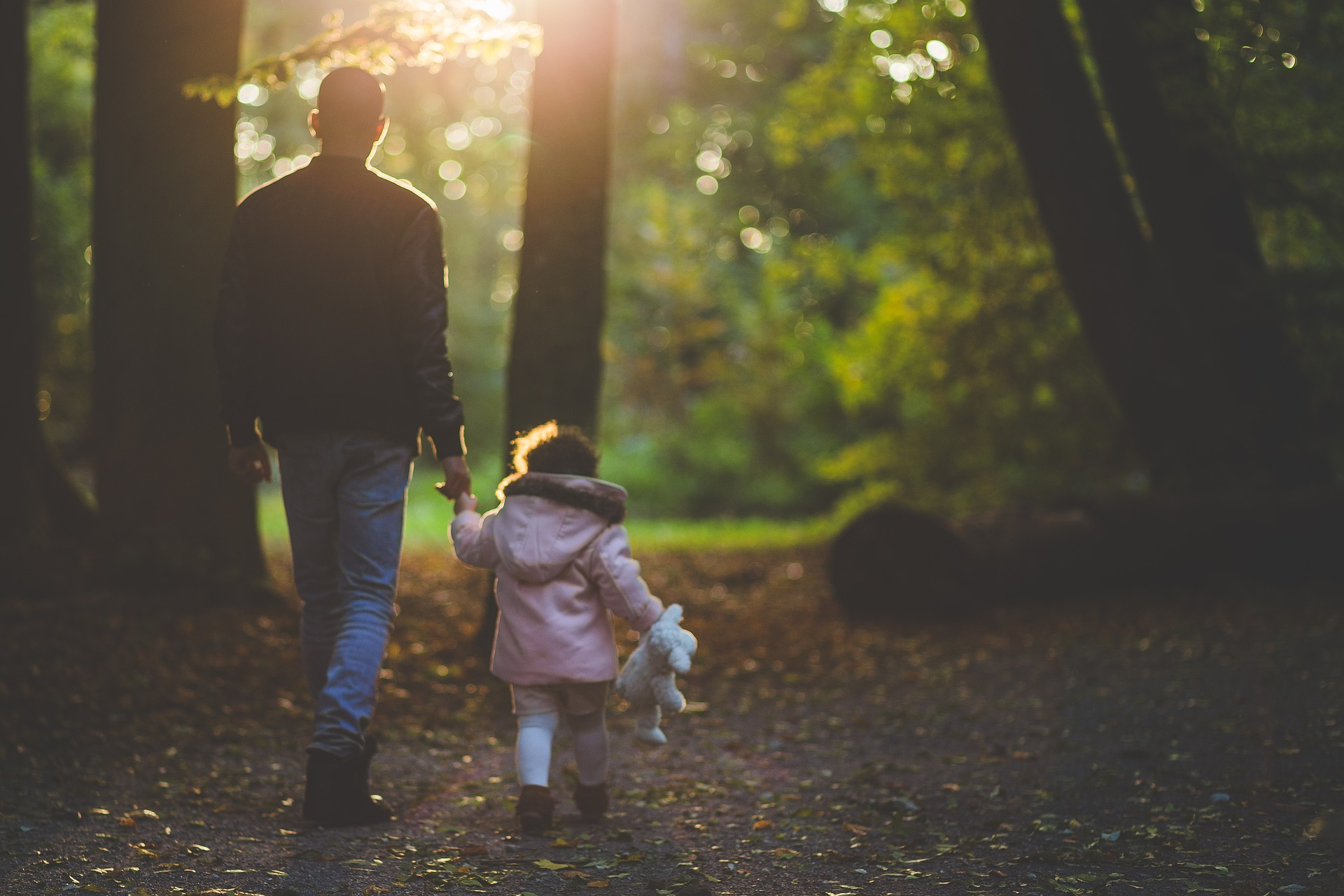 photo of father and daughter walking through woods